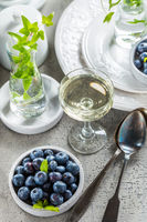 Dining room table decorated with small vase with ivy. Place setting with plates and bowl with blueberries and glass of wine.