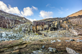 Old stone quarry with waterfall in Mourne Mountains near Slieve Donard mountain