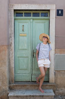 Beautiful young female tourist woman wearing sun hat, standing and relaxing in shade in front of vinatage wooden door in old Mediterranean town while sightseeing on hot summer day