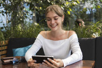 Photo of beautiful lady sitting in cafe and making selfie with a smart phone. Portrait of young smiling student girl make video call from smartphone to her best friend, having break, telling good news, sitting in cafe.