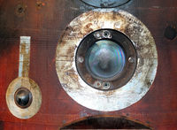 close up of a round porthole on a used russian space re-entry vehicle with burned red and black steel panel