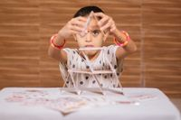 Young girl kid busy in building Pyramid with house of cards at home - concept of focus or concentration excerise game for school children