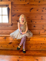 A little red head girl sitting on a wooden stairs