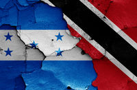 flags of Honduras and Trinidad and Tobago painted on cracked wall