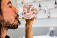 man enjoy the taste of white wine glass