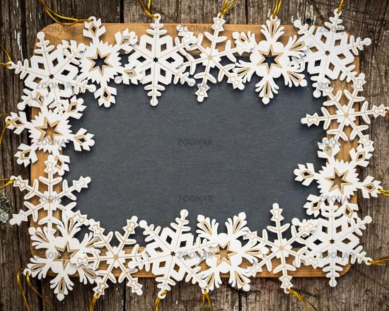 Blackboard blank framed in wooden snowflakes