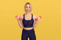 Pretty blond woman with pink dumbbells