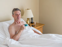 Single caucasian senior man in inclined bed and smiling toward viewer