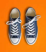Blue sneakers isolated on orange background