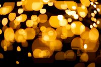 Yellow spots of light against black background