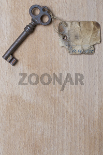 Antiker Schlüssel mit Anhänger auf Holz