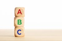 ABC letters alphabet on wooden blocks stacked on wood table. Copy space