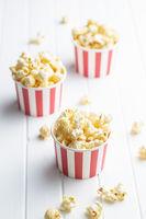 Sweet tasty popcorn in striped paper cup.
