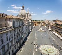 Top view of Piazza Navona in Rome with a crowd of unrecognizable tourists on a sunny day.