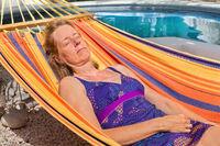 Caucasian woman relaxing in hammock near pool