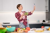 Pretty woman happy taking selfie using her smartphone while cooking fresh salad wearing a plaid shirt with a bob hair style. Healthy food leaving - vegan concept