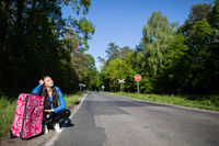 Bored of waiting to hitchhike, a teenager waits at the side of a road leading through a leafy forest on a sunny day.