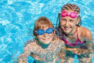 Kids having fun playing around in swimming pool.