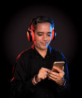 Indian Man listening to music on wireless headphones with a mobile in hand