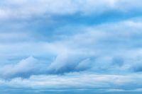 low dark blue clouds in spring evening sky