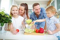 Familie und Kinder machen Salat in Küche