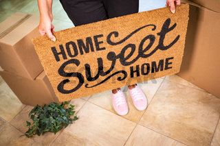 Woman in Pink Shoes Holding Home Sweet Home Welcome Mat, Boxes and Plant