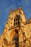 side view of one of the towers at the front of york minster in sunlight against a blue cloudy sky
