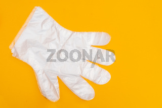 Transparent white protective gloves on yellow background. Protective clothing.