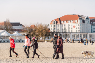 Poland, Sopot, February 9, 2020. People jogging on beach. Nordic walking. Winter season at seaside. Winter Walk on Beach. People chill out in cold season on coast. crowd walking on beach in Sopot