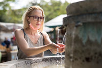 Thirsty young casual cucasian woman wearing medical face mask drinking water from public city fountain on a hot summer day. New life during covid epidemic