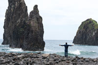 Man with arms wide open looking at Ribeira da Janela islet in Madeira