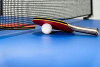 Red table tennis paddle white ball and a net