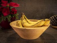 Gedrechselte rustikale helle Holzschale mit Bananen steht auf einer dunklen Unterlage mit Blumen im