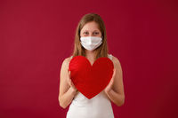 Smiling woman wearing face mask and holding red heart in hands.