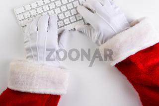 High angle closeup of Santa Claus hands using his computer keyboard.