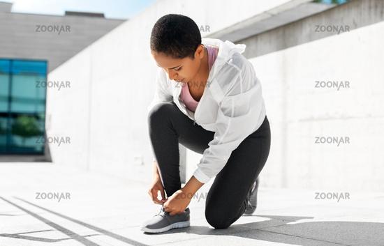 african american woman tightening sneakers