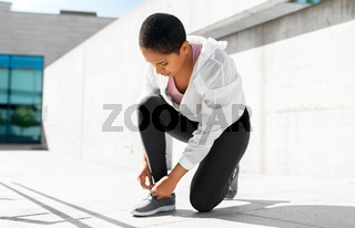african american woman tightening sneakers