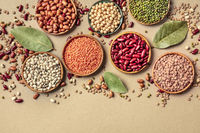 Legumes assortment, shot from the top on a rustic brown background with a place for text. Lentils, soybeans, chickpeas, red kidney beans, a vatiety of pulses with bay leaves