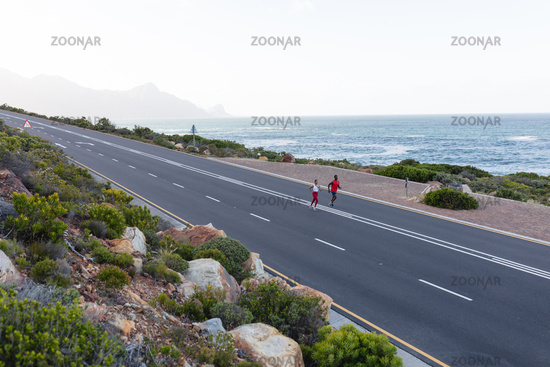 Fit african american couple in sportswear running on a coastal road