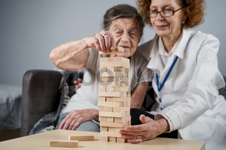 Mature doctor conducting session, therapy for senior patient in nursing home, training fine motor skills for dementia, alzheimer disease and recovery institute by folding wooden blocks, playing jenga