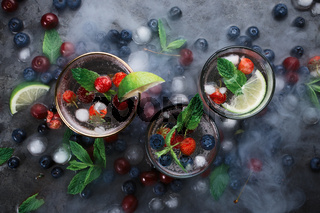 Flatlay of three cups with iced soda water on dark background with mint