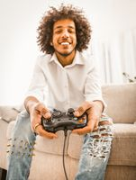 Funny gamer play computer games sitting alone at home in self isolation during quarantine period. Young Arabic guy holds joystick or gamepad. Focus on male hands in foreground. Tinted image