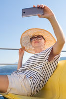 Beautiful, romantic blonde woman taking selfie self portrait photo on summer vacations traveling by cruse ship ferry boat.