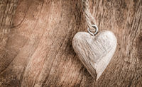 Small wooden heart on wooden background in vintage style. Symbol of love.