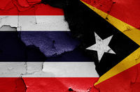 flags of Thailand and East Timor painted on cracked wall