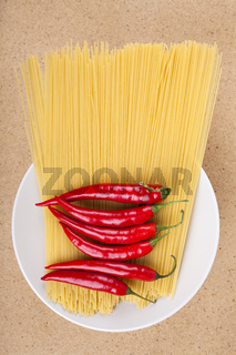 Chili peppers and uncooked pasta on plate