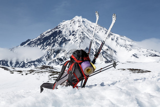 Backpack, skis and poles lie on snow on background volcano