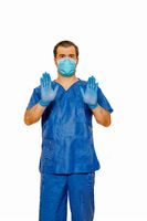 Male doctor in scrubs with protective face mask and gloves showing stop sign with both hands