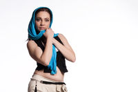 Young woman in beige pants, black vest with blue scarf