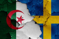 flags of Algeria and Sweden painted on cracked wall